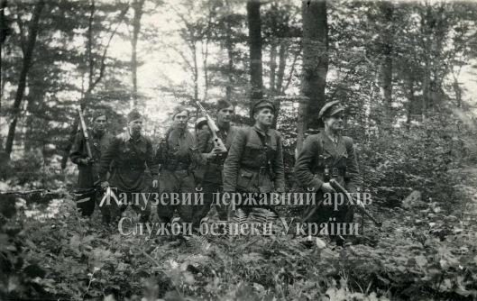 Група зв'язкових Головного командира УПА В. Кука йде в лісі. 1952 рік.1. Демян. 2. Орач. 3. Байда. 4. Довбуш. 5. Тарас. 6. Петро.
